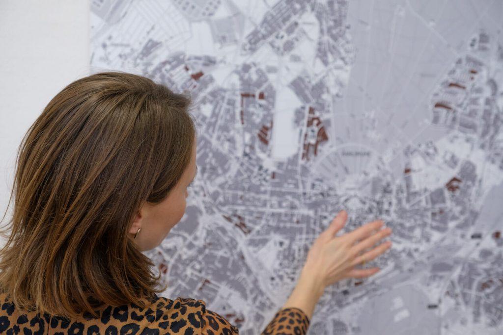 Pia Hesselschwerdt blickt auf einen Stadtplan von Karlsruhe